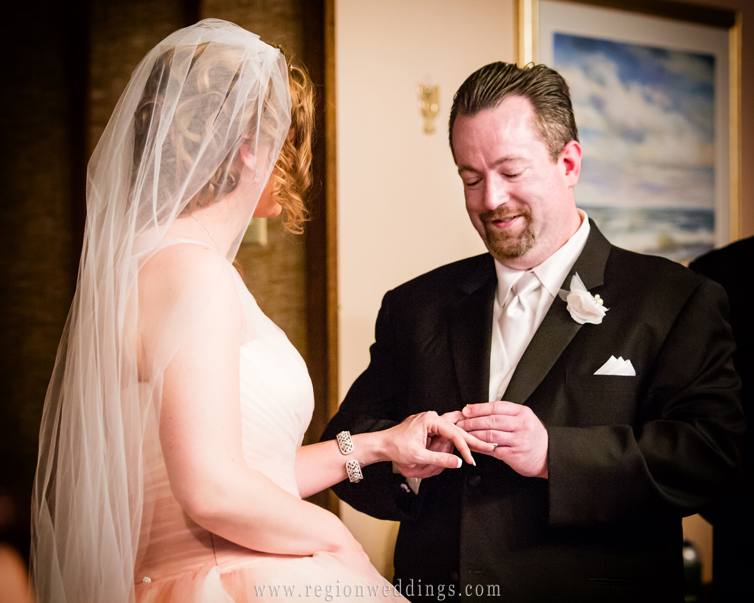 The groom places the ring upon his bride at a wedding ceremony at Free Spirit Church.