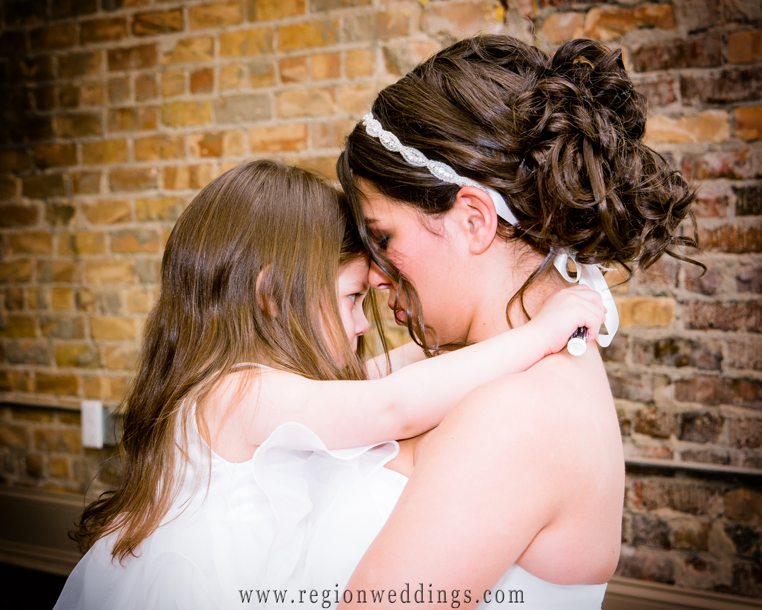 The flower girl gives her mom, the bride, a hug just before her wedding at The Allure in LaPorte, Indiana.
