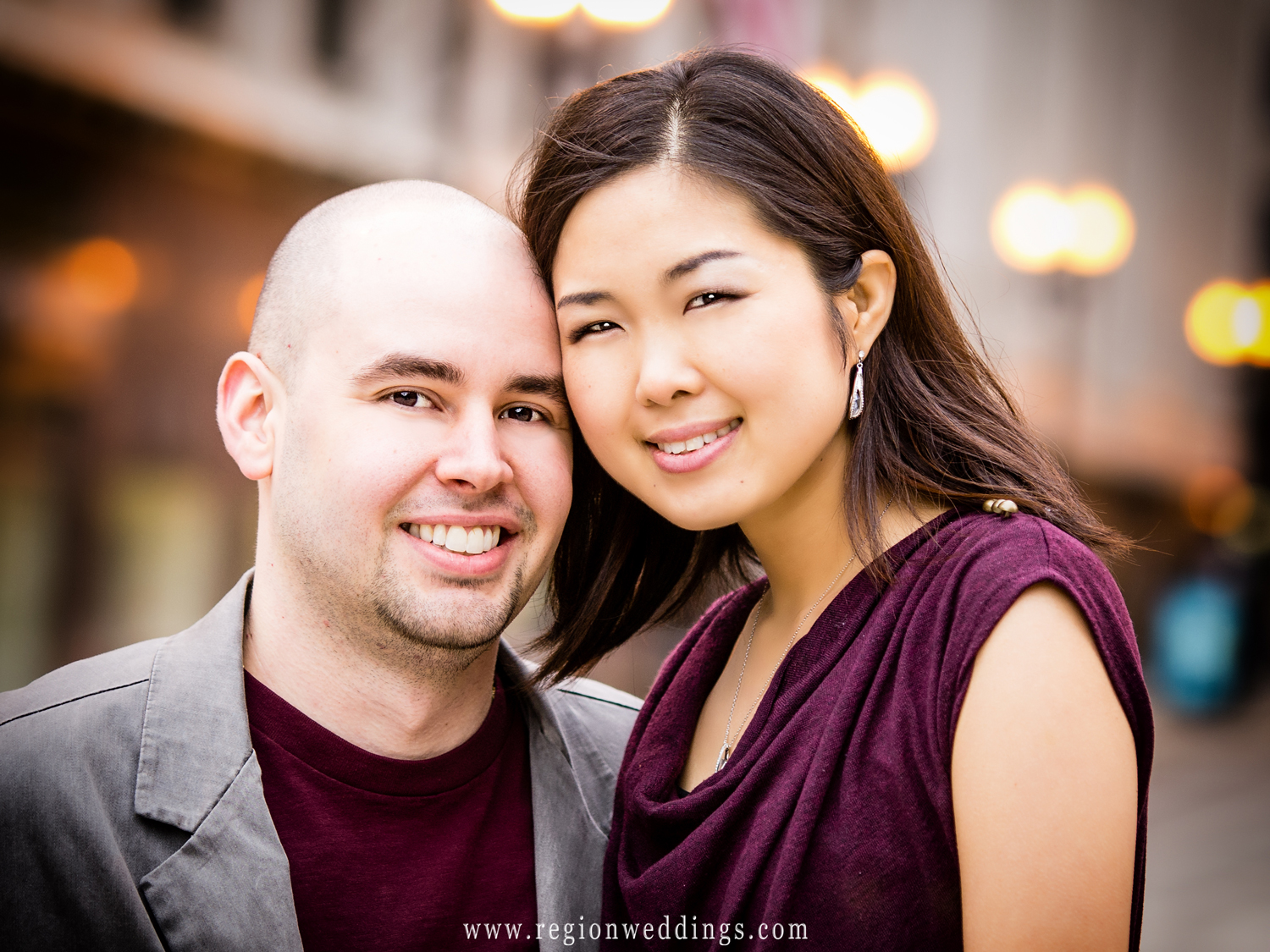 A cute couple poses on the streets of Chicago for a close up engagement portrait with street lights of the city in the background.