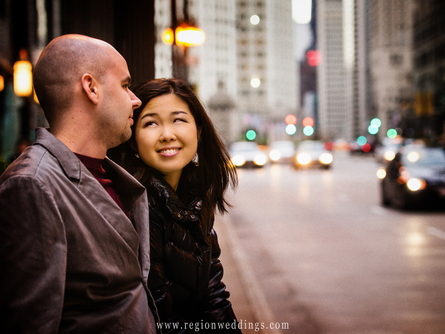 A couple gazes at each other on Michigan Avenue during their engagement photo session as night begins to fall with car headlights as the background.