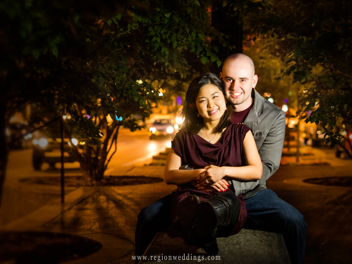 A couple poses on a bench in downtown Chicago for this romantic night time engagement photo.