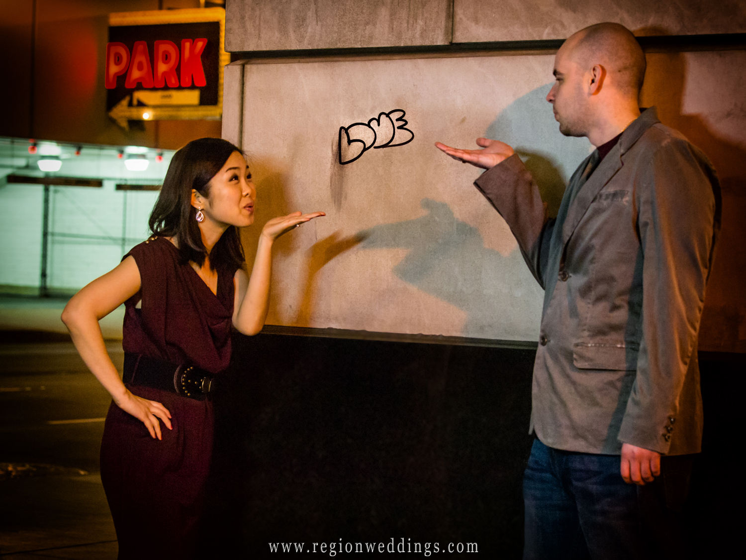A romantic couple blows kisses to each other in downtown Chicago during their night time engagement photo session.