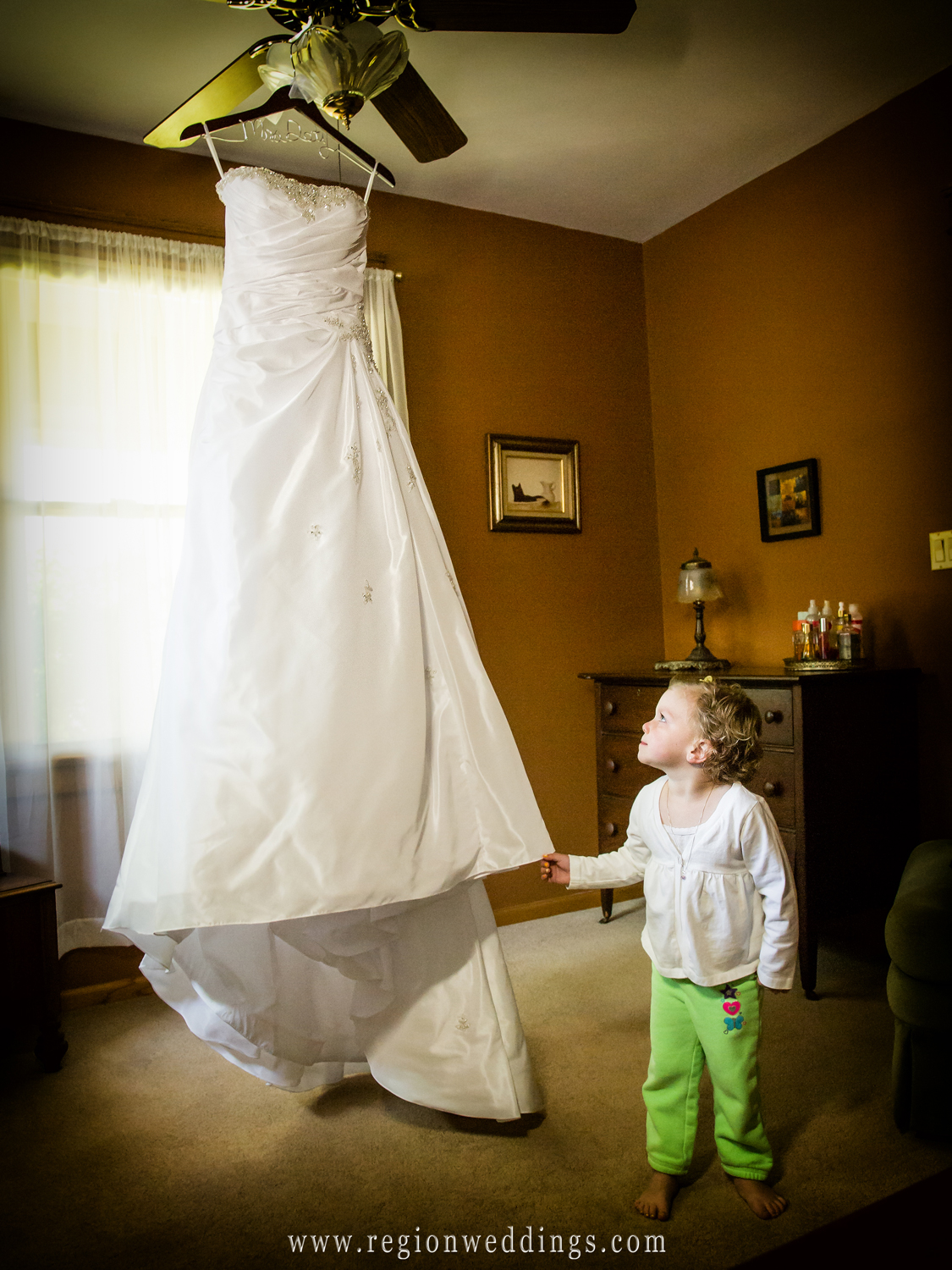 The flower girl looks up at the bride's hanging dress in the cute wedding photo.