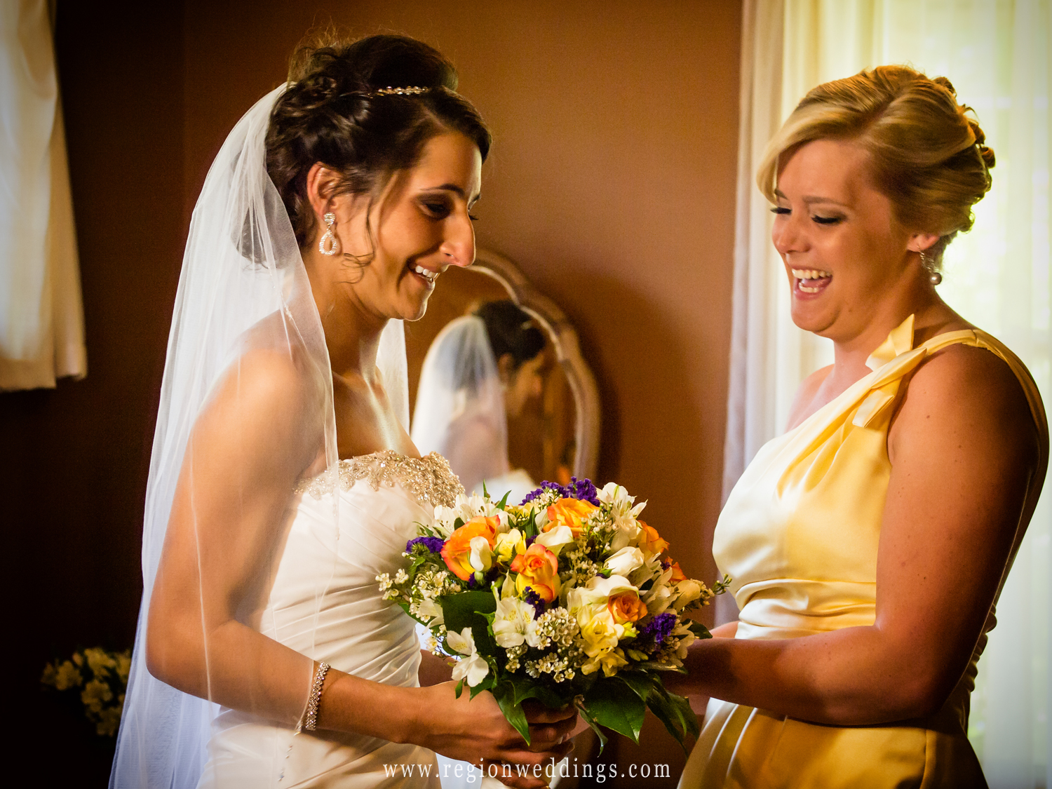 A fun moment is captured on the wedding day between the bride and her maid of honor.