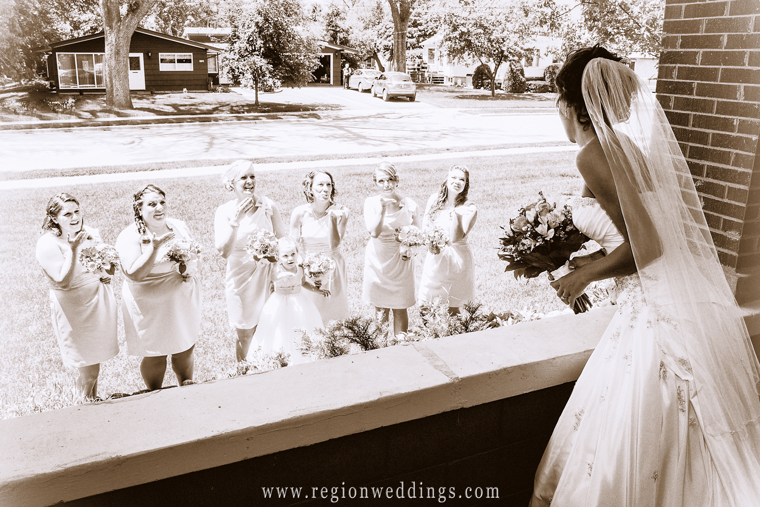 The bridesmaids blow kisses toward the bride after seeing her for the first time in her wedding dress.