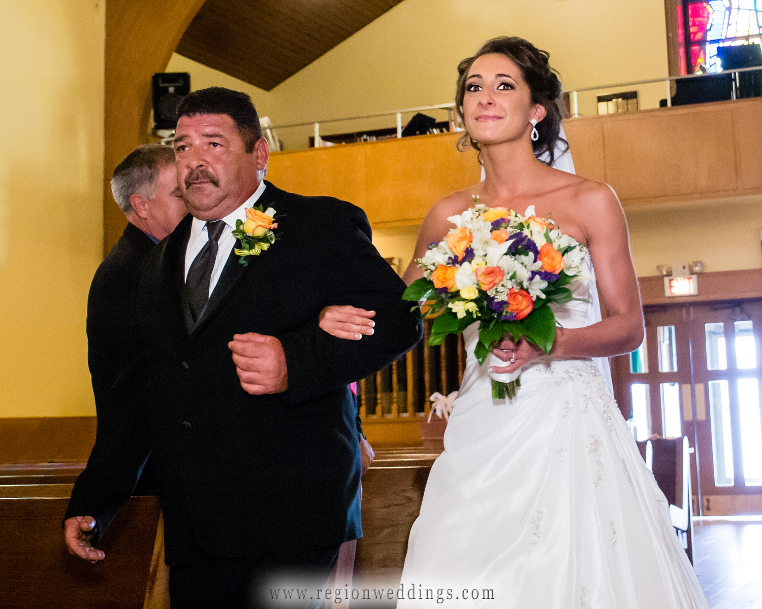 The father of the bride walks his daughter down the aisle at the Parish of St. Joseph in Homewood, Illinois.