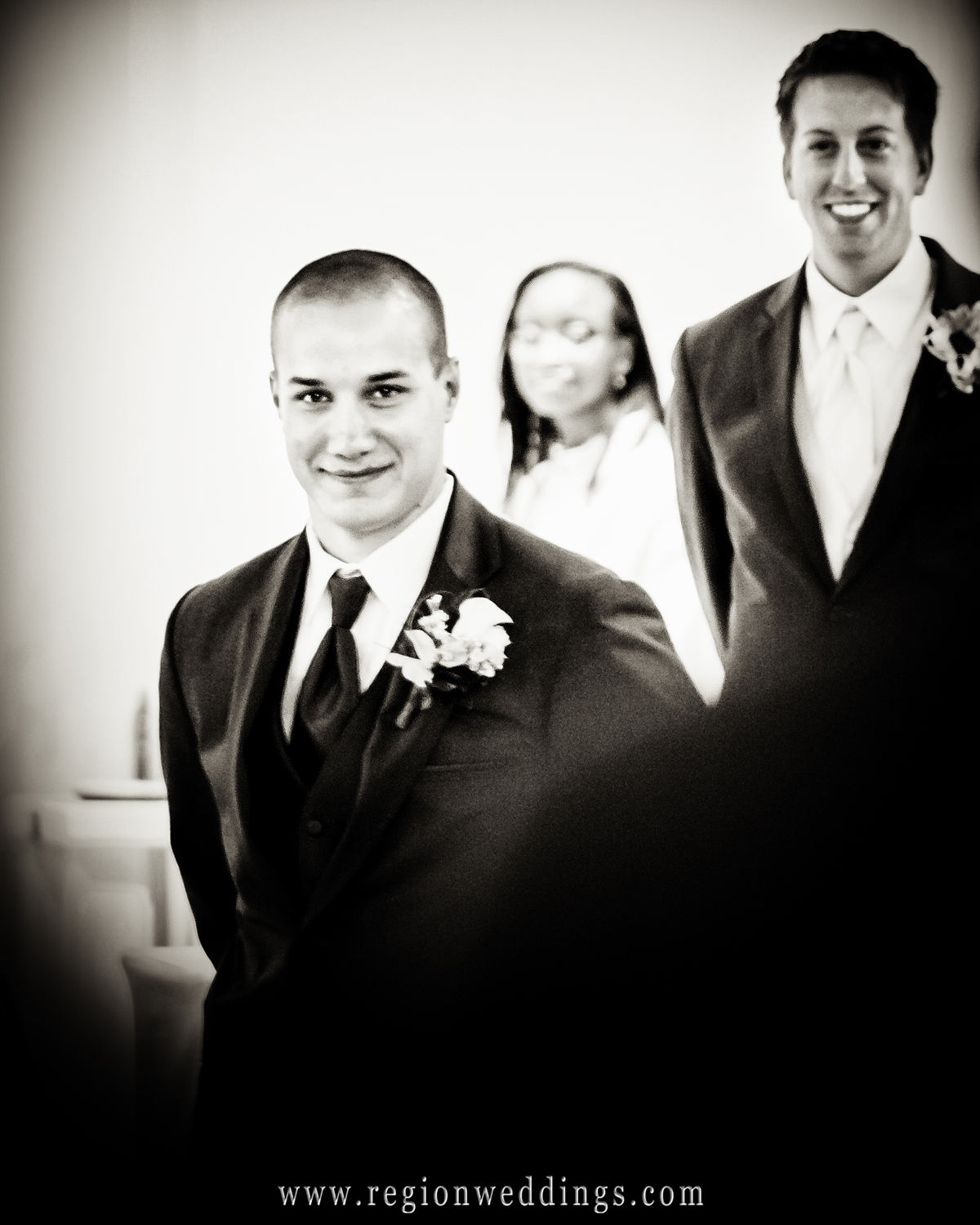 The groom looks on happily as his new bride comes down the aisle at their June wedding in Homewood, Illinois.