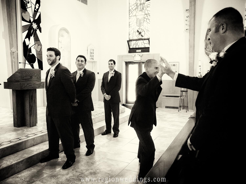 A groomsmen provides a fun wedding moment as he high fives an audience member at a church wedding.