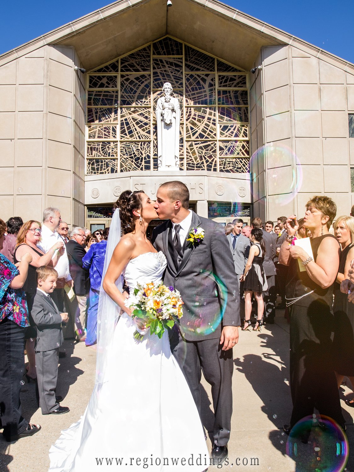 The bride and groom leave church as guests blow bubbles upon them.