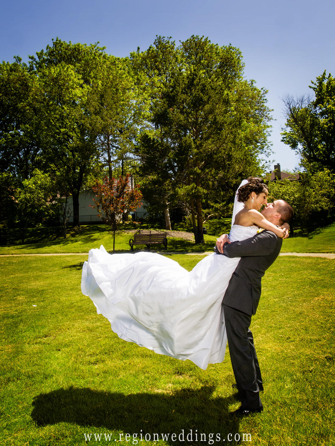 The groom lifts his bride into the air for their summer wedding photos in Homewood, Illinois.