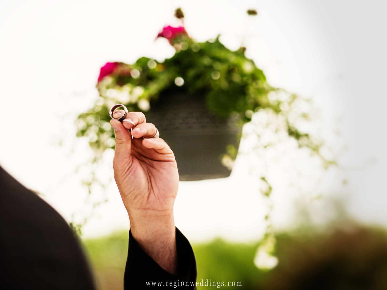 A pastor holds up the wedding rings at an outdoor wedding ceremony at White Hawk Country Club in Crown Point, Indiana.