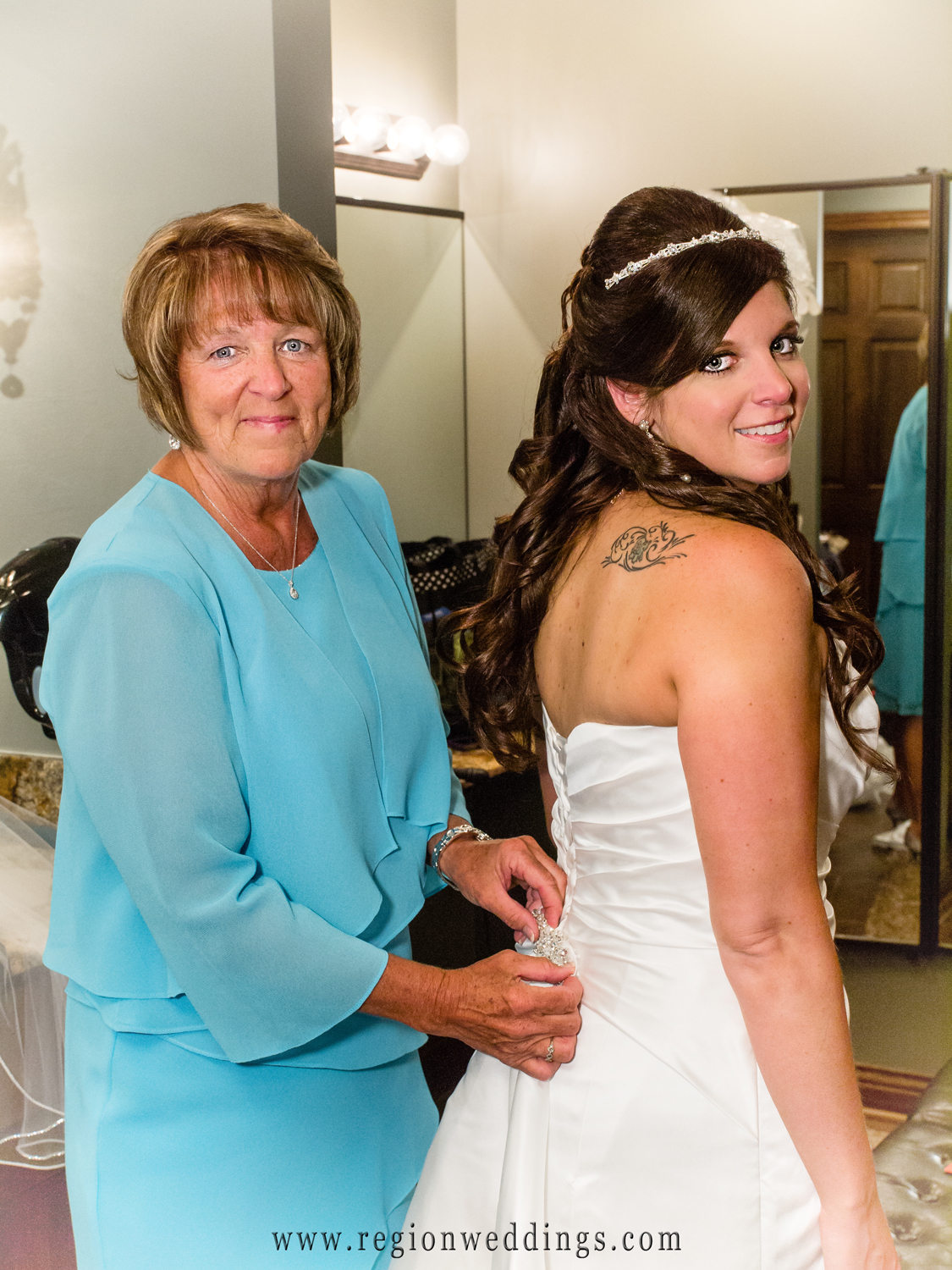 The mother of the bride helps her daughter into her wedding dress.