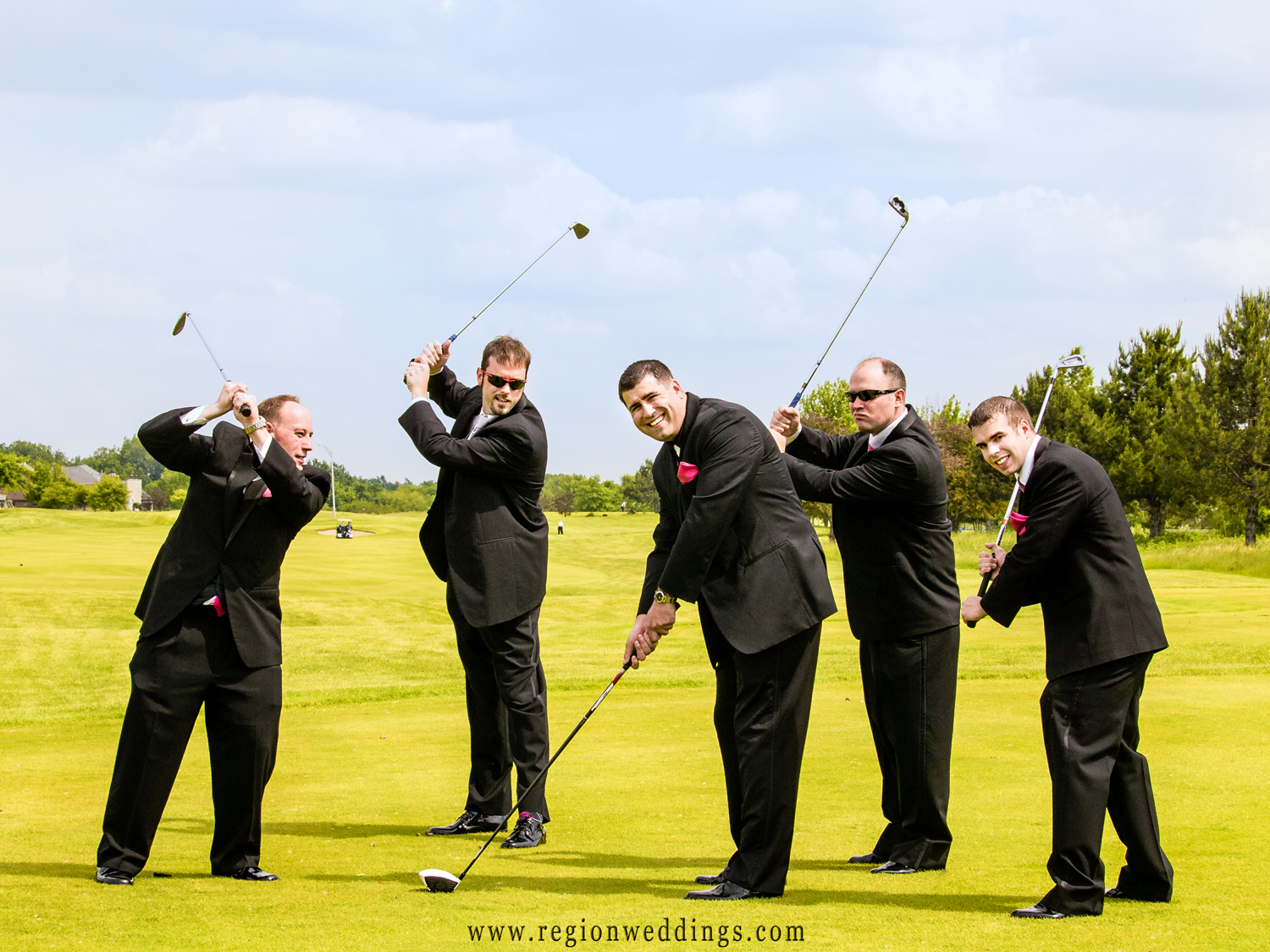 The groomsmen attack the groom with golf clubs for this fun wedding photo at White Hawk Country Club.