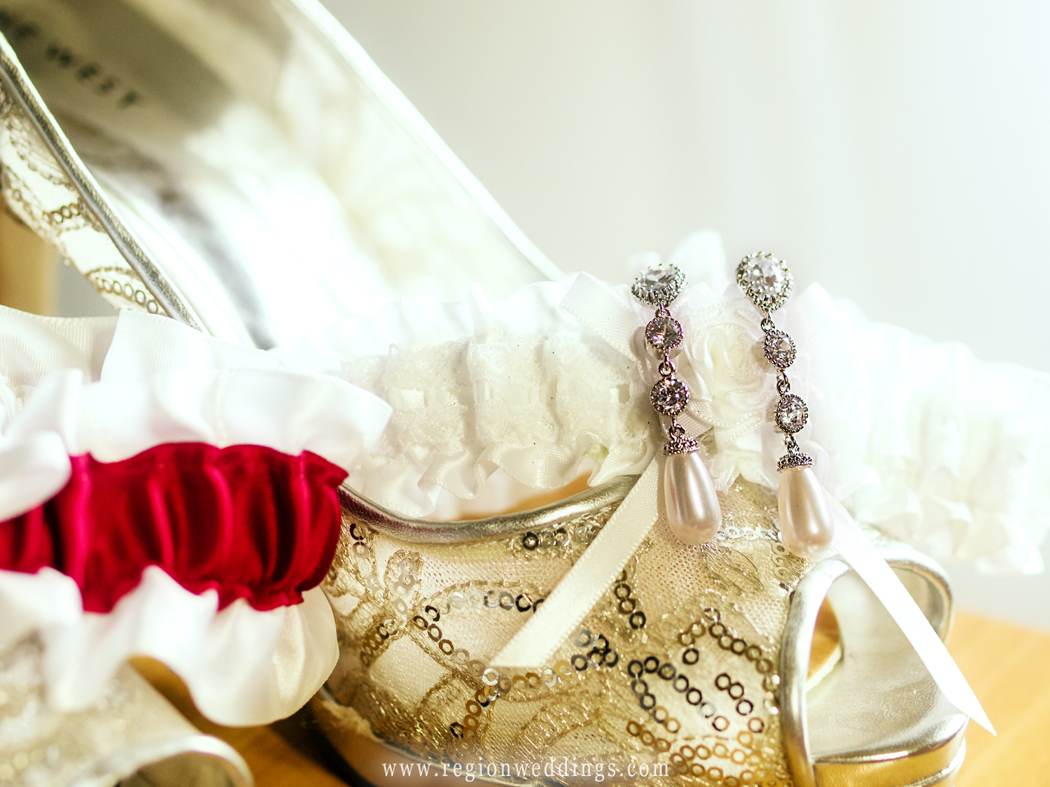 The bride's earrings are draped over her garter and her shoes with her wedding dress in the background.