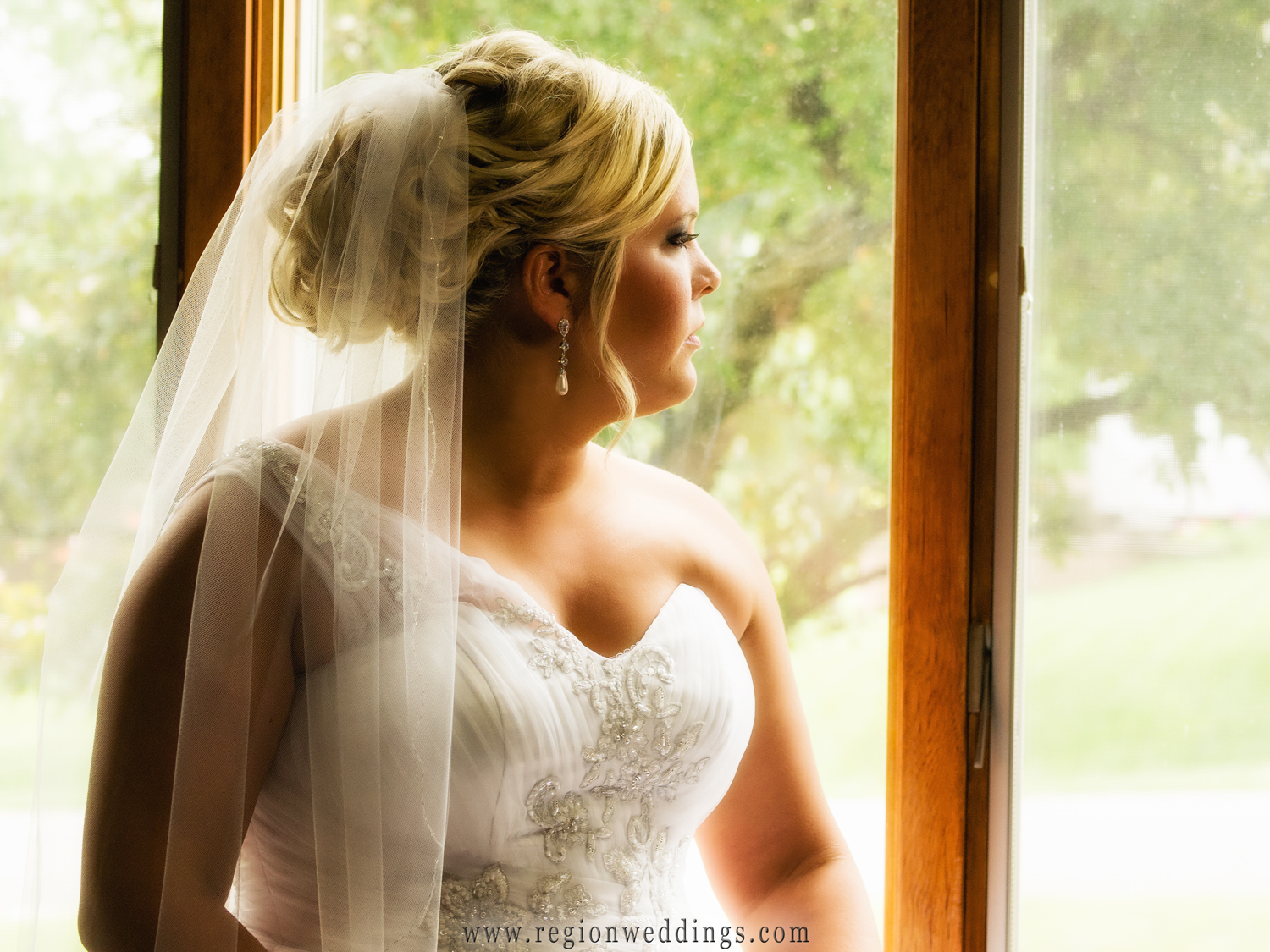 The bride looks out the window of her childhood home as sun bathes her in warm light illuminating her beautiful wedding veil.
