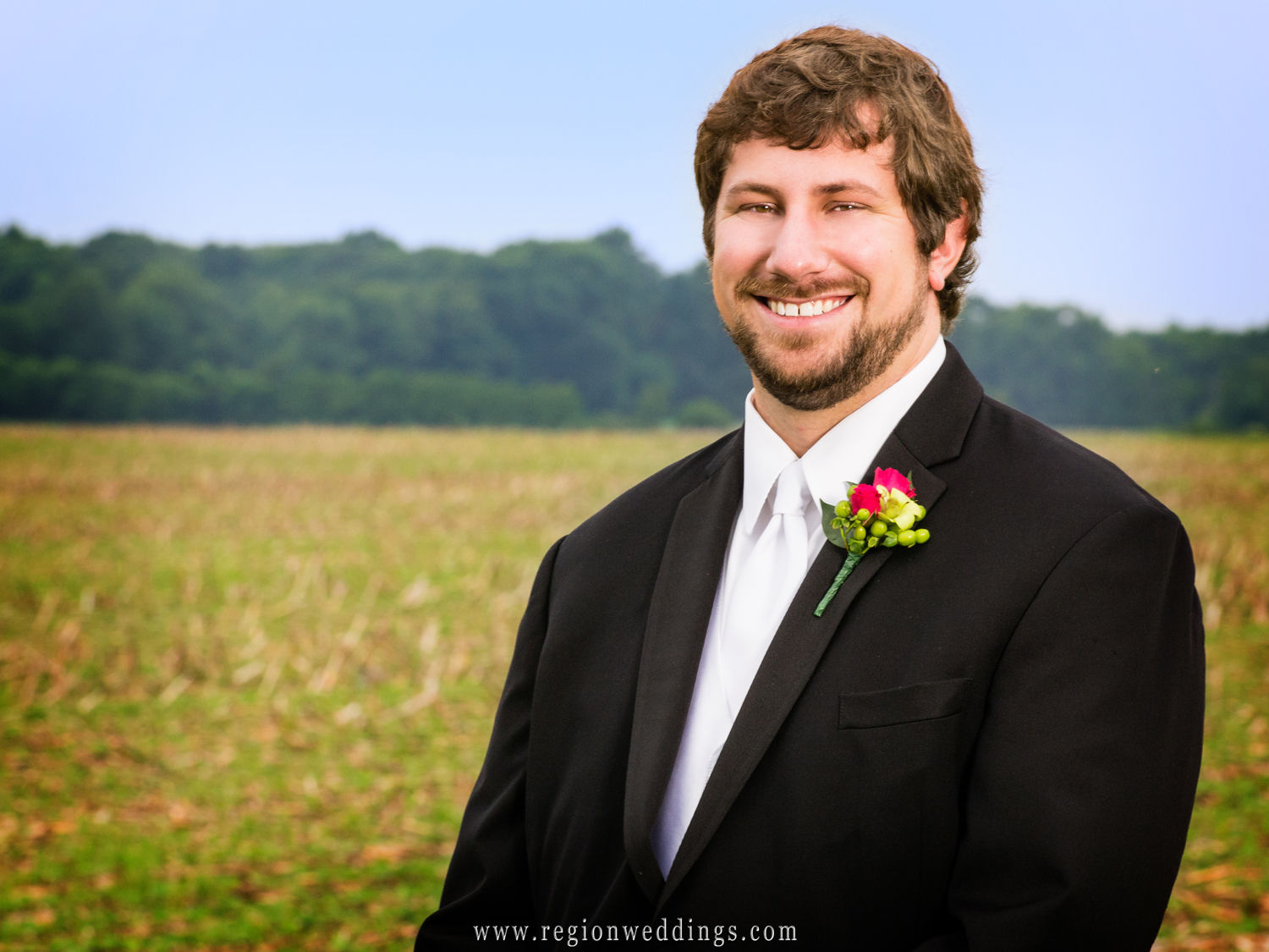 The groom smiles for his wedding portrait amongst the farm land outside Saint Elizabeth Ann Seton Church in Valparaiso, Indiana.