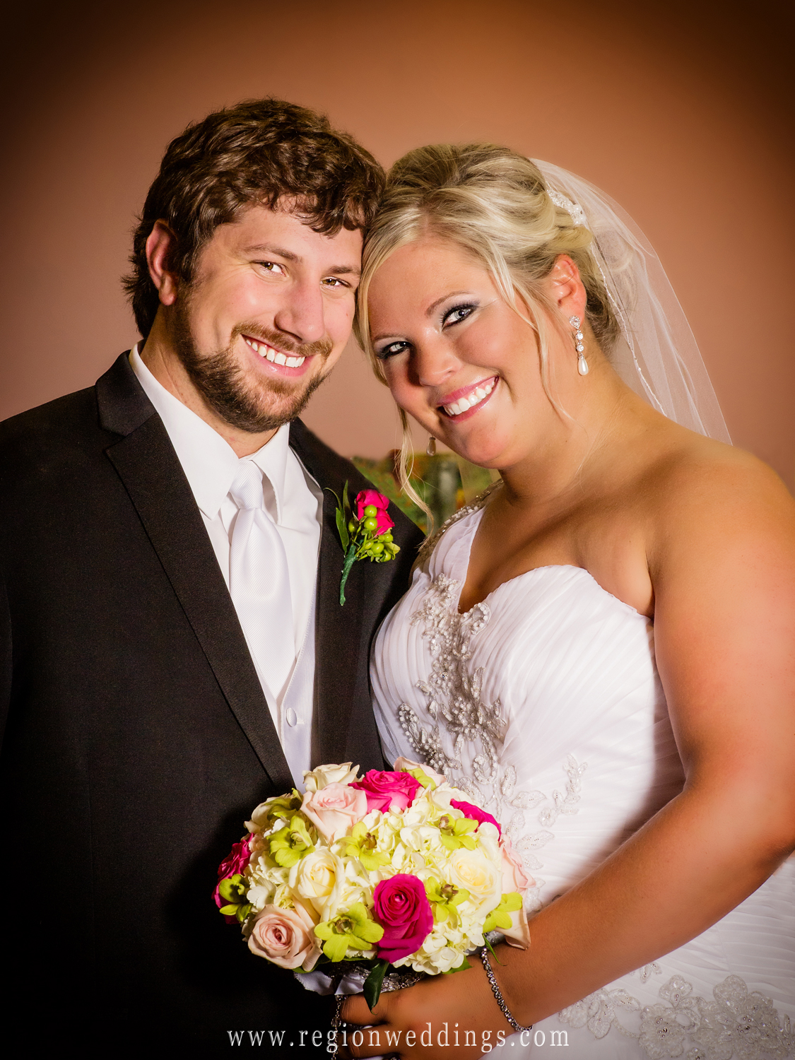 A formal wedding photo of the bride and groom at the altar of St. Elizabeth Ann Seton Church in Valparaiso.