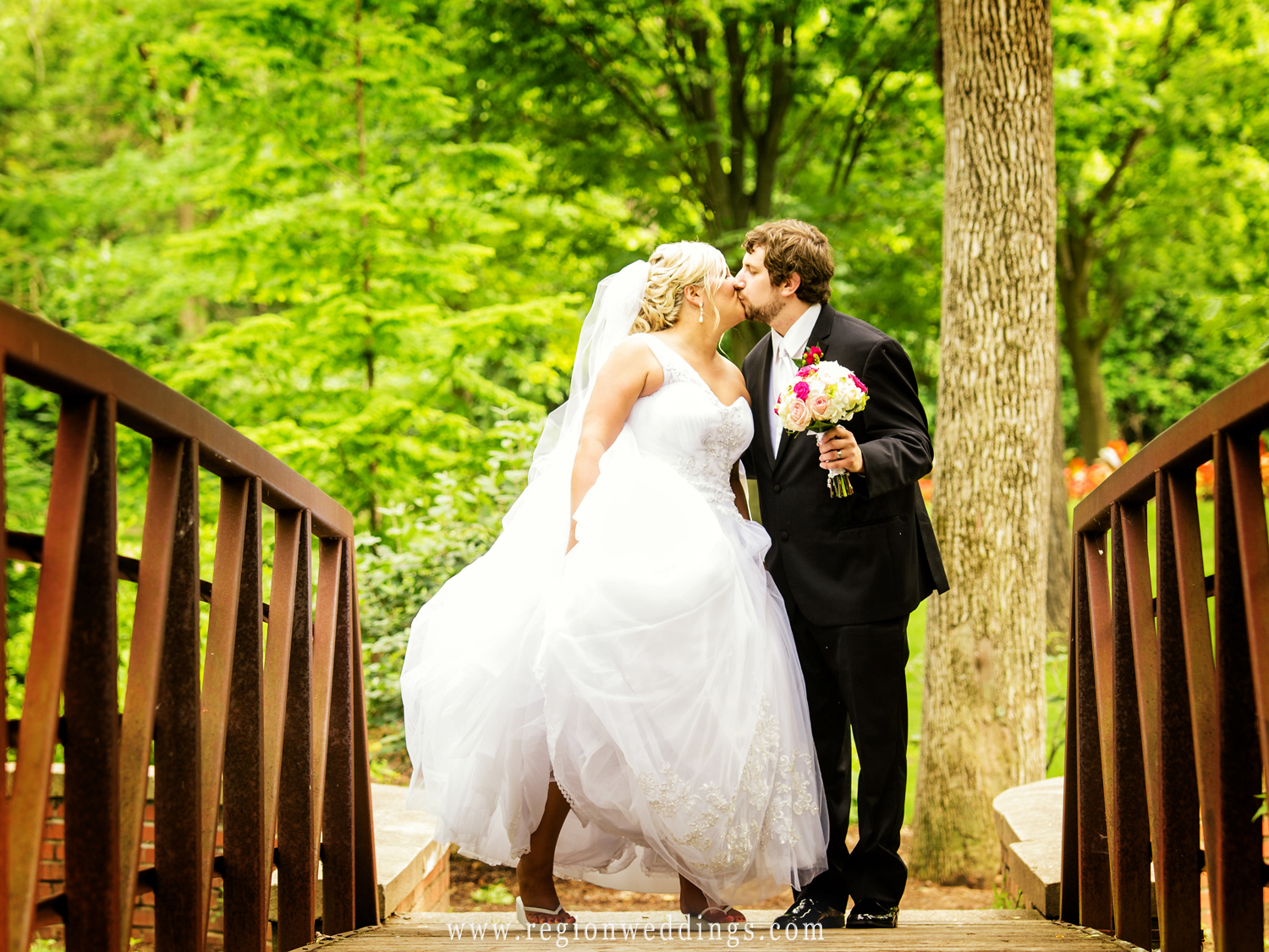 Bride and groom kiss as they cross over the bridge at Deep River Park in Hobart, Indiana.