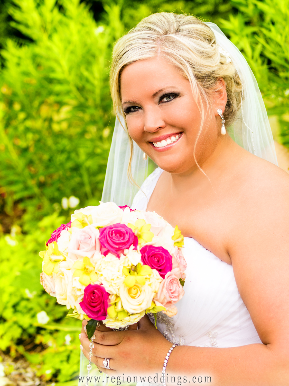 Bride holds her summer bouquet of wedding flowers in the garden at Aberdeen Manor in Valparaiso, Indiana just after her wedding.