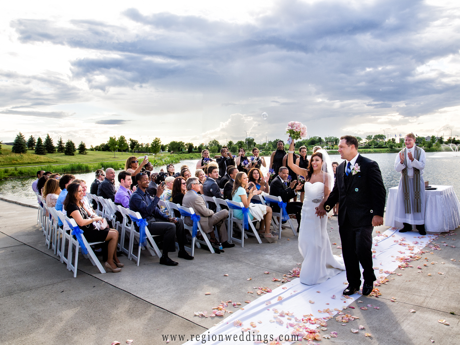 A just married couple waves to friends and family after their summer wedding in Munster, Indiana.