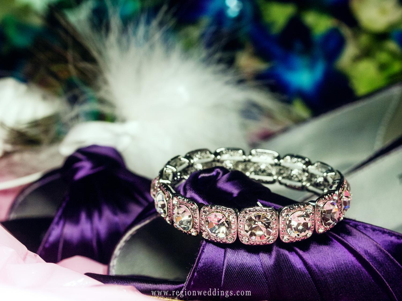 The bride's wedding bracelet sits upon her purple wedding shoes.