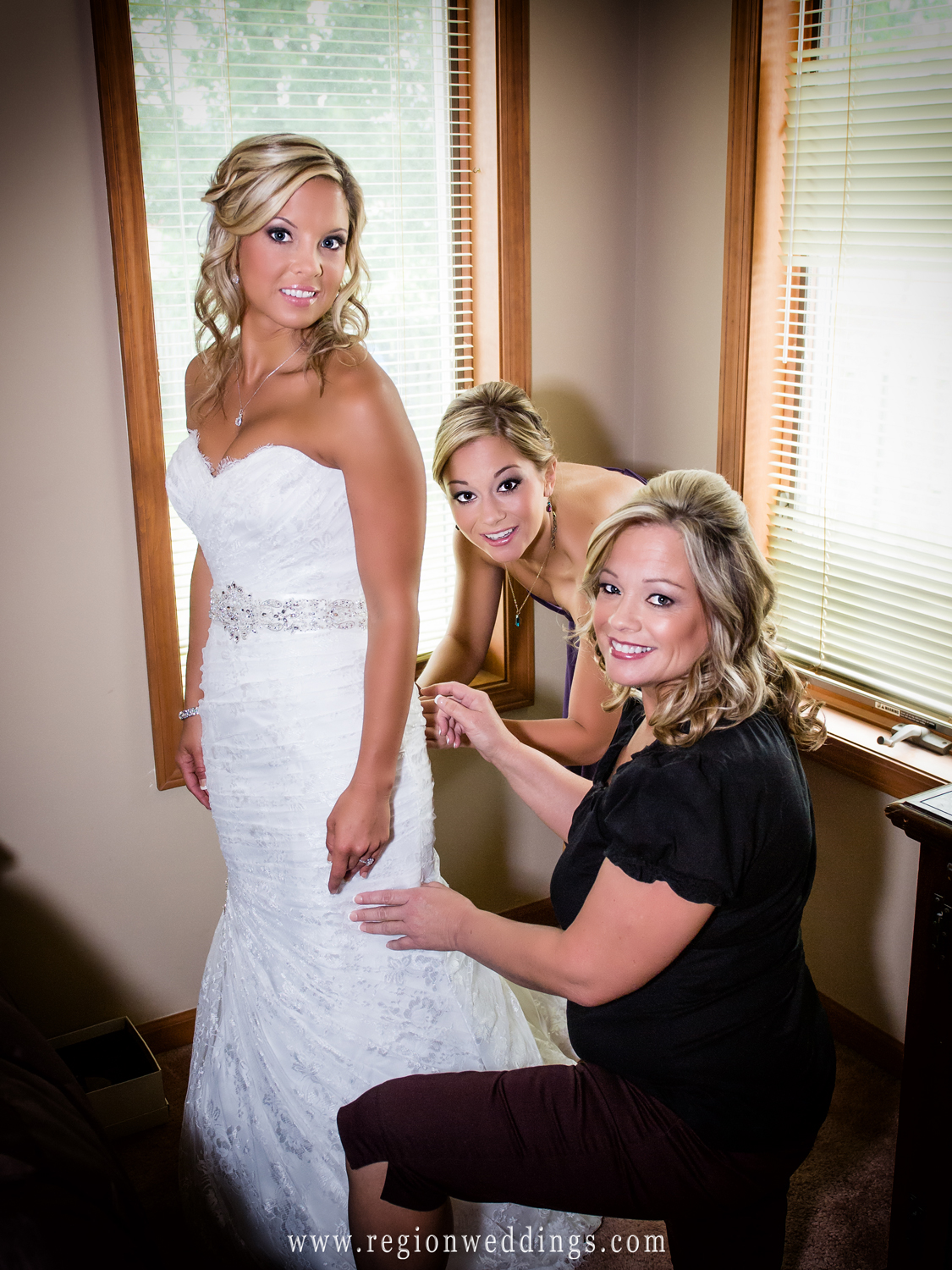The bride's mom and sister help her into her wedding dress.