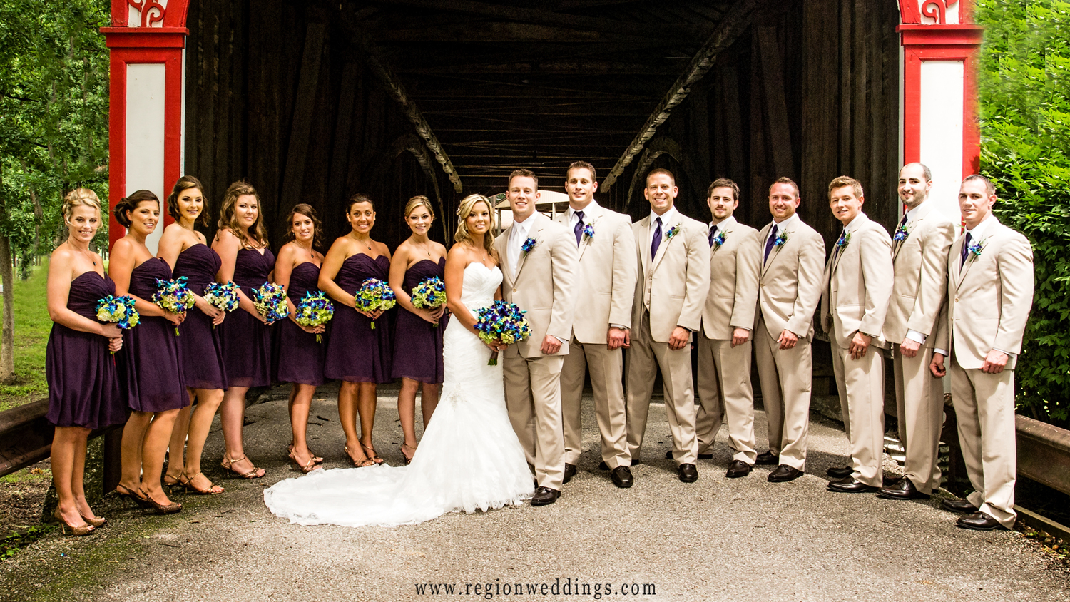 The entire wedding party has their photo taken in front of the the Old Covered Bridge at the Lake County Fairgrounds in Crown Point.