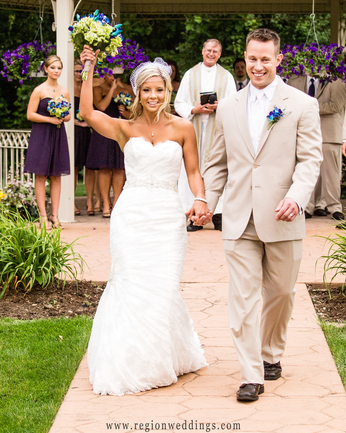 A newly married couple celebrates as they walks down the aisle at their outdoor summer wedding at Halls of St. George.