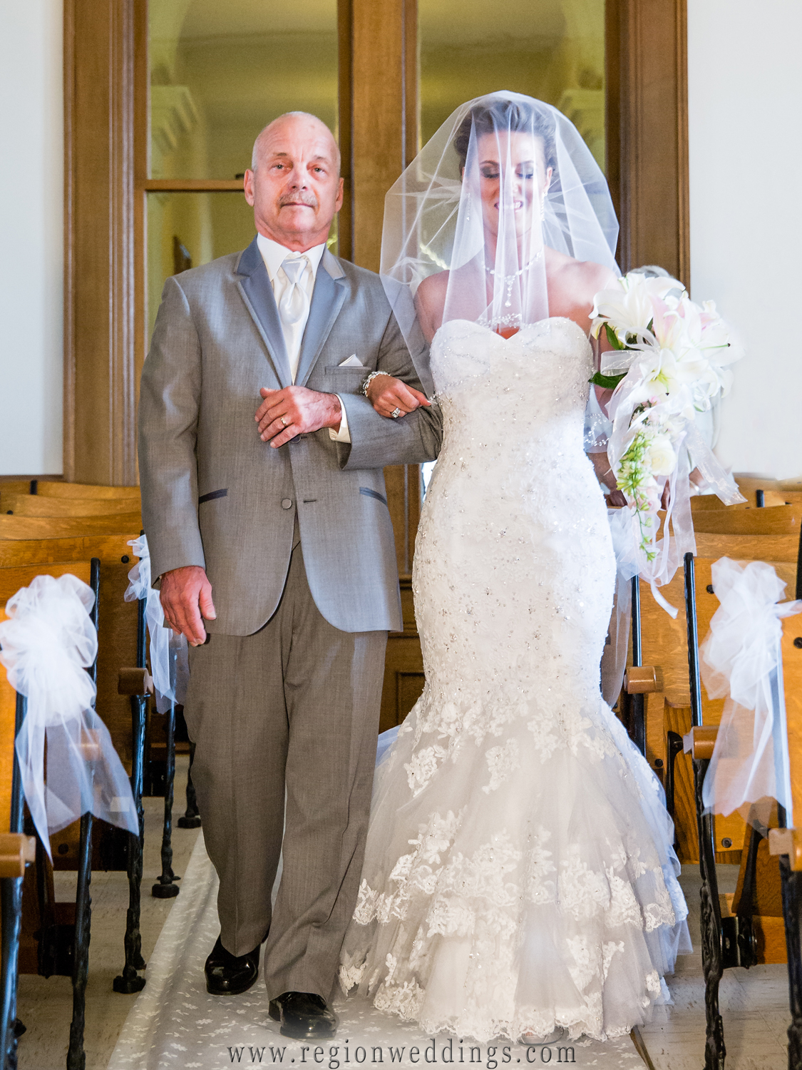 Father of the bride walks her down the aisle of the old Crown Point courthouse.