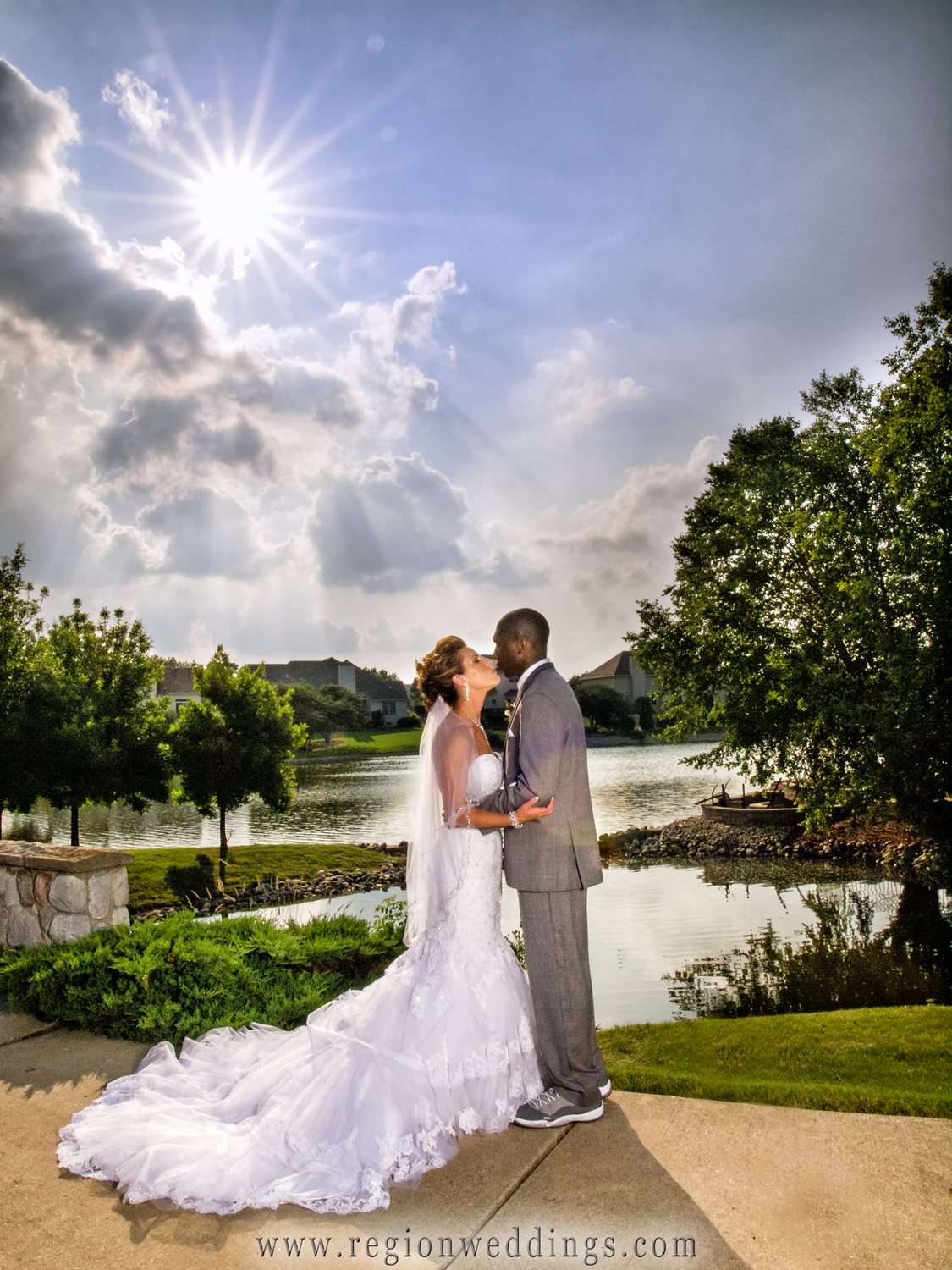 A sunburst appears in the sky as the bride and groom look toward each other in this romantic wedding photo at Ellendale Farm in Crown point.