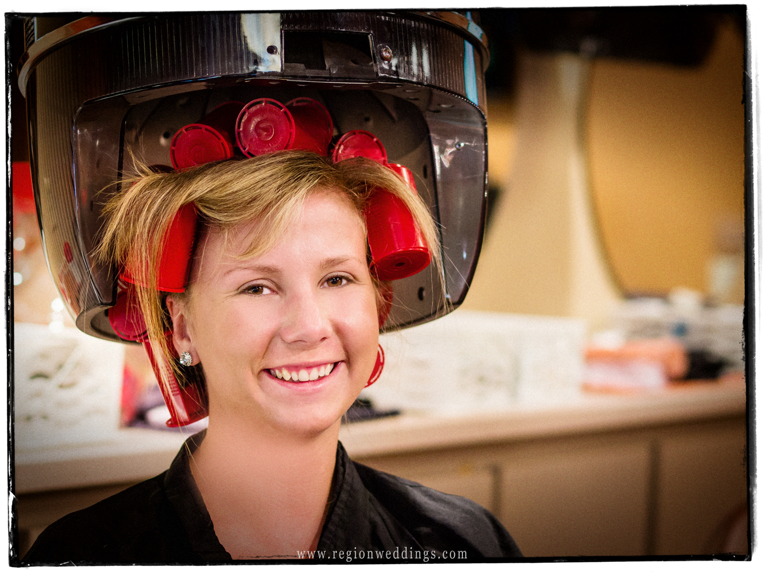 Bridesmaid smiles as she poses for a photo in curlers and under an old fashioned hair dryer.
