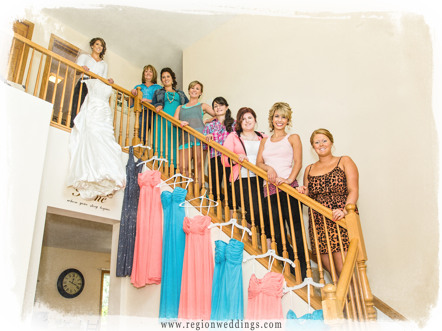 The bride and her bridesmaids pose on stairs overlooking their wedding day dresses.