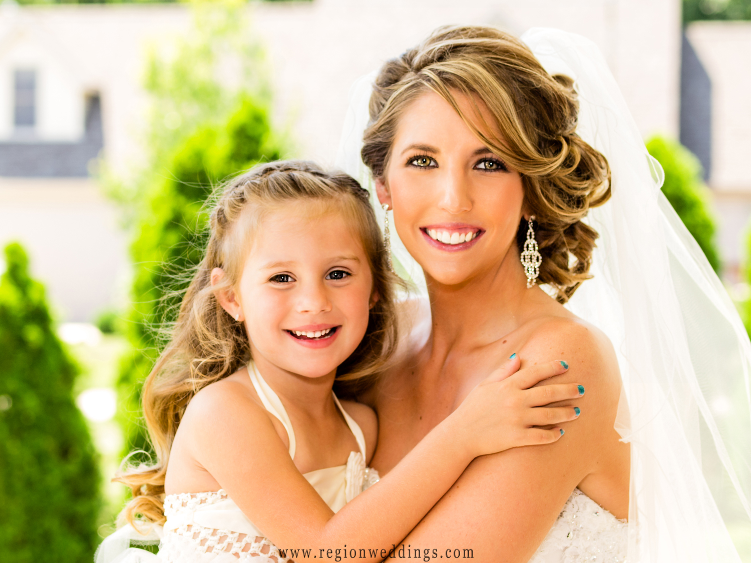 The flower girl hugs the bride for their wedding day portrait.