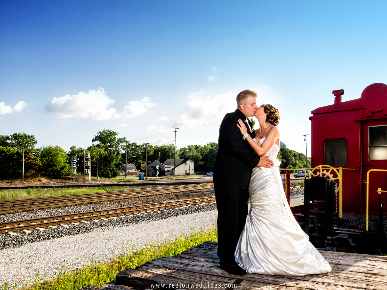 The bride and groom kiss on top of a railroad car in downtown Griffith, Indiana.