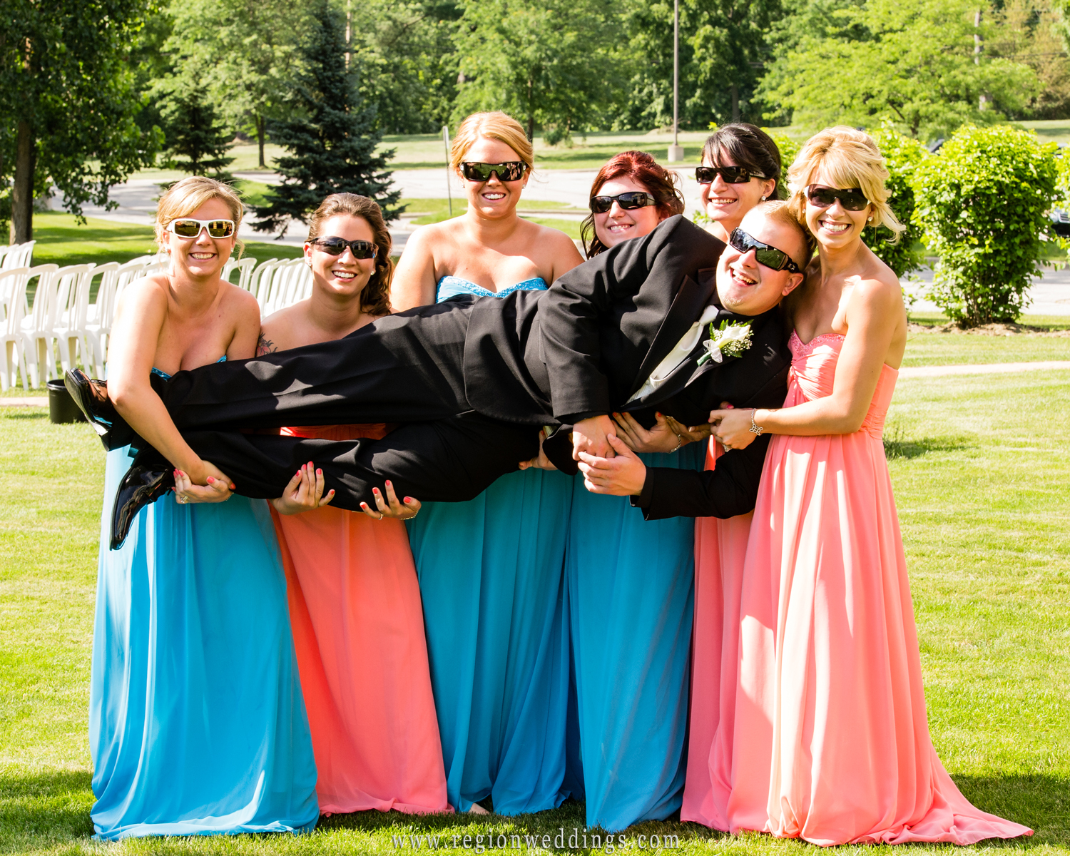 Bridesmaids carry the groom while wearing sun glasses at an outdoor wedding at the Halls of St. George.