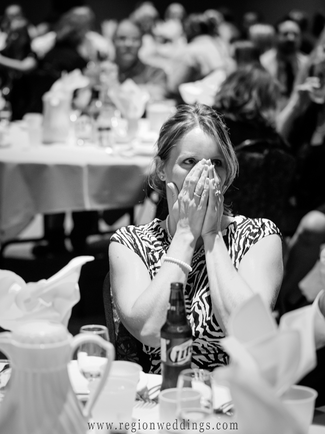A wedding guest face-palms her laughter at one of the speeches given at the reception.