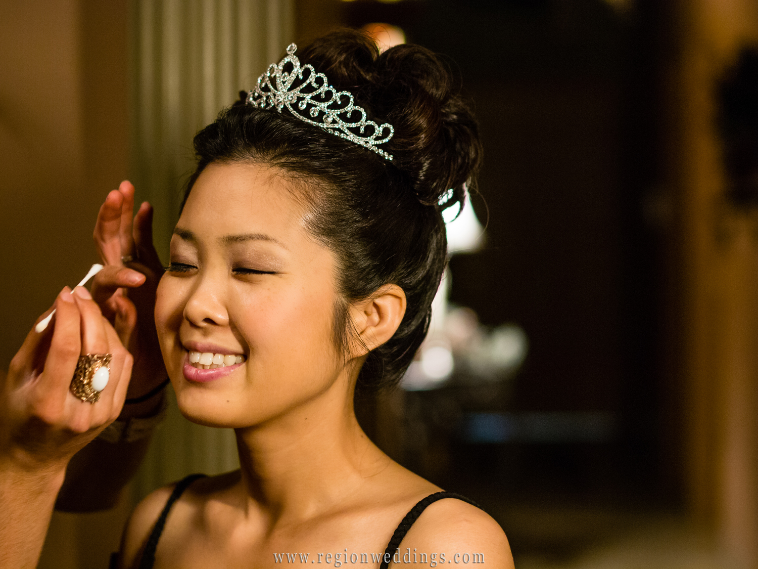 A Korean bride smiles as she is pampered before her wedding by a stylist at Robert Anthony Hair Design.