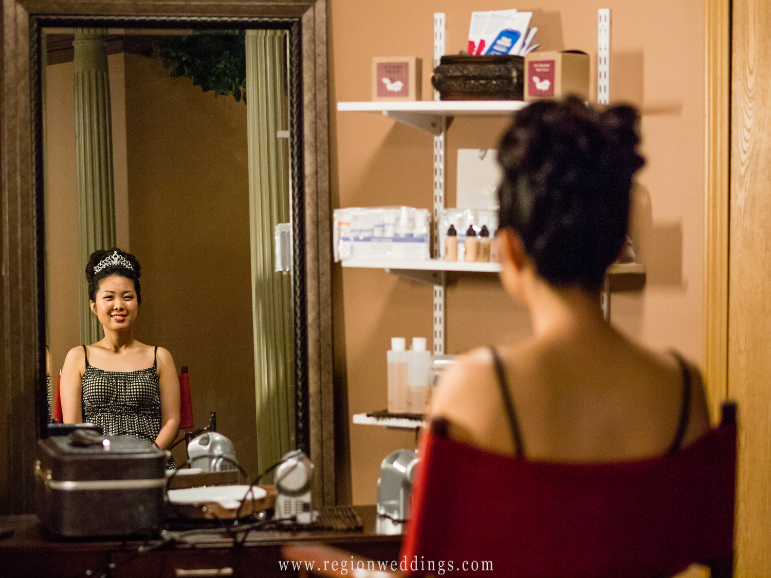 An Asian bride smiles as she sits inside a spa in Northwest Indiana on her wedding day.