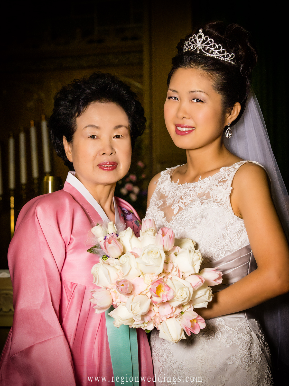 A Korean bride's mother poses with her daughter wearing traditional clothing for a wedding photo in Crown Point, Indiana.