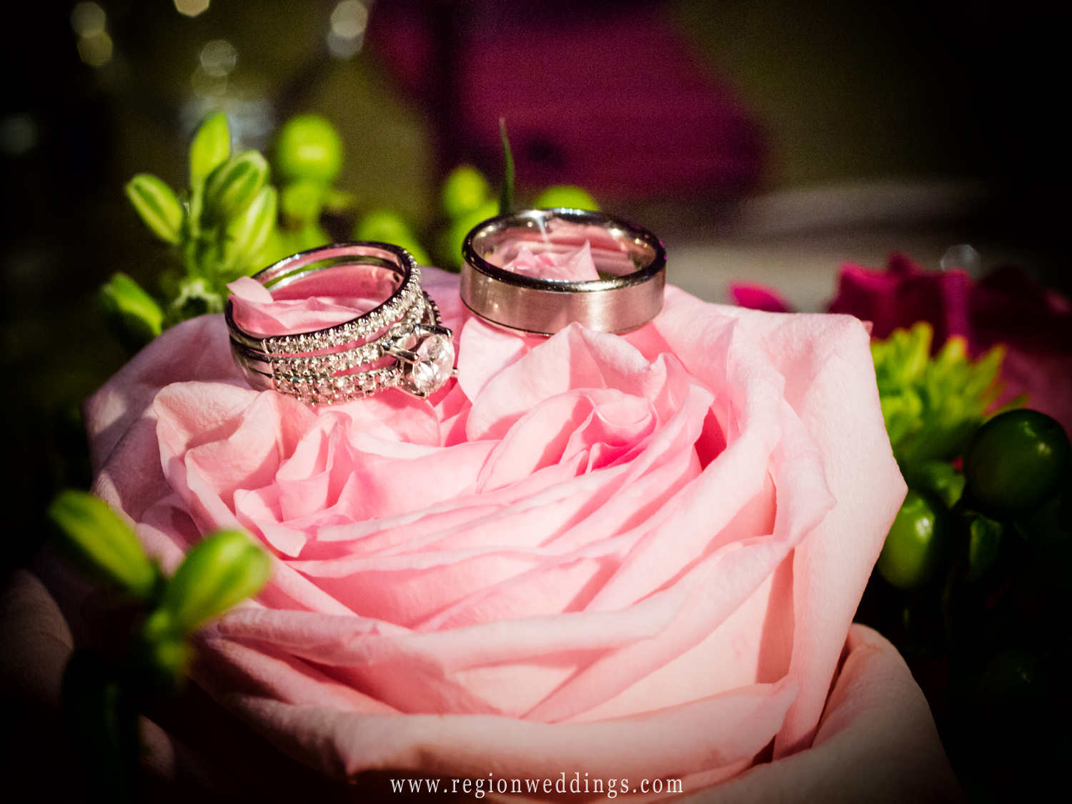 Wedding ring photograph featuring the bride's bouquet of flowers.