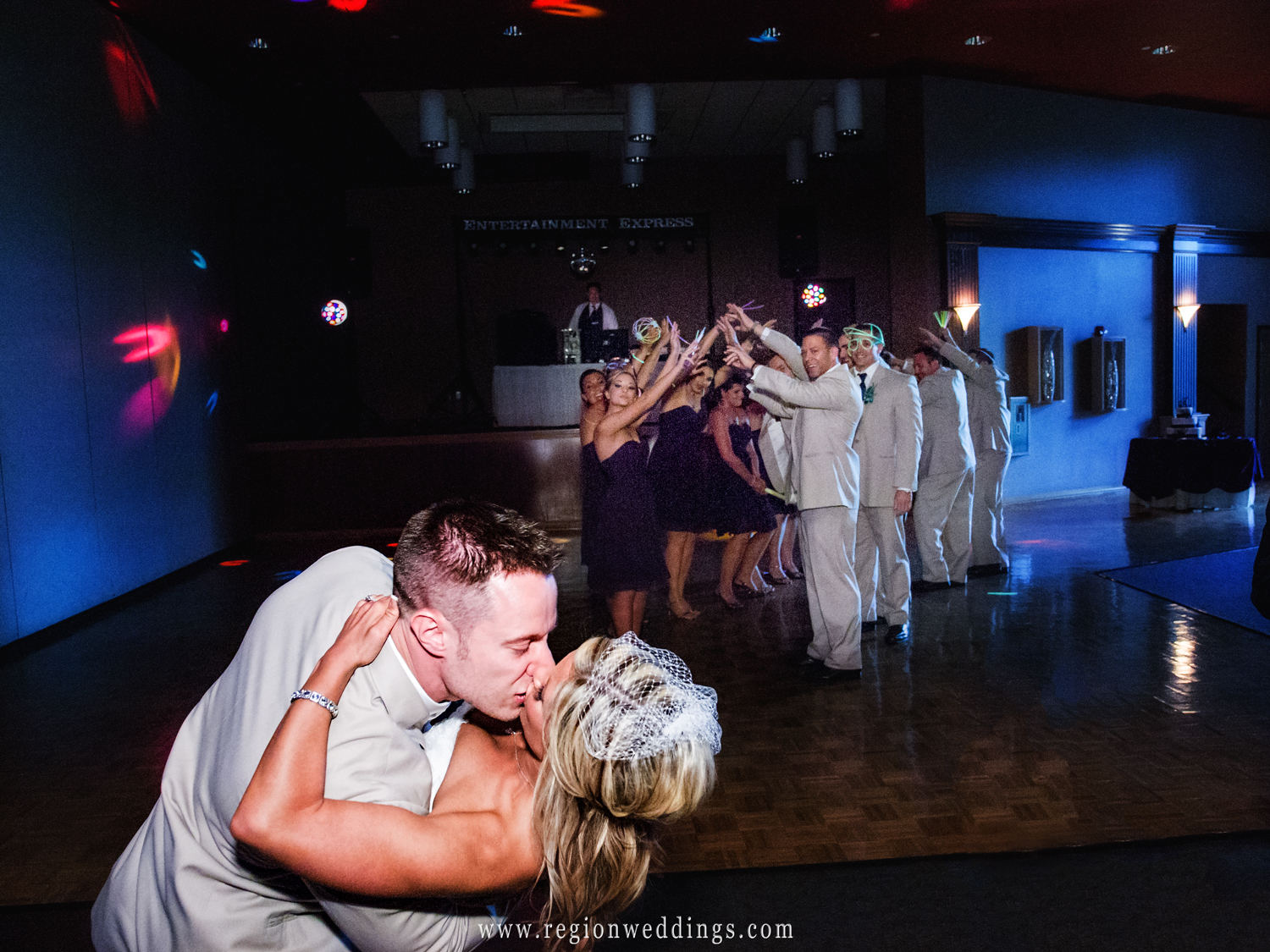 A groom dips his bride on the dance floor at the Halls of St. George during their introduction.