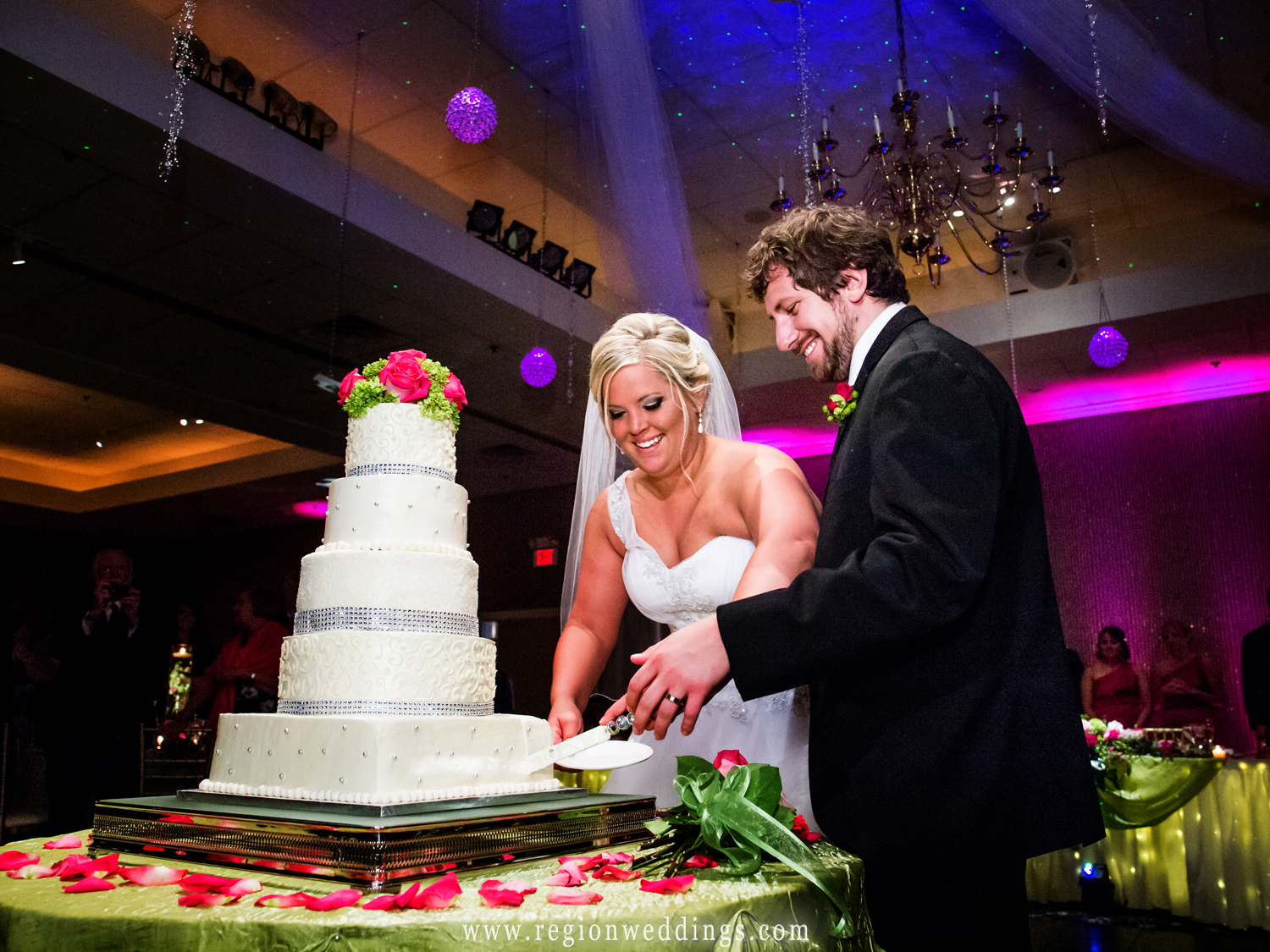 The bride and groom cut their cake at Aberdeen Manor in Valparaiso with stunning uplighting in the background.