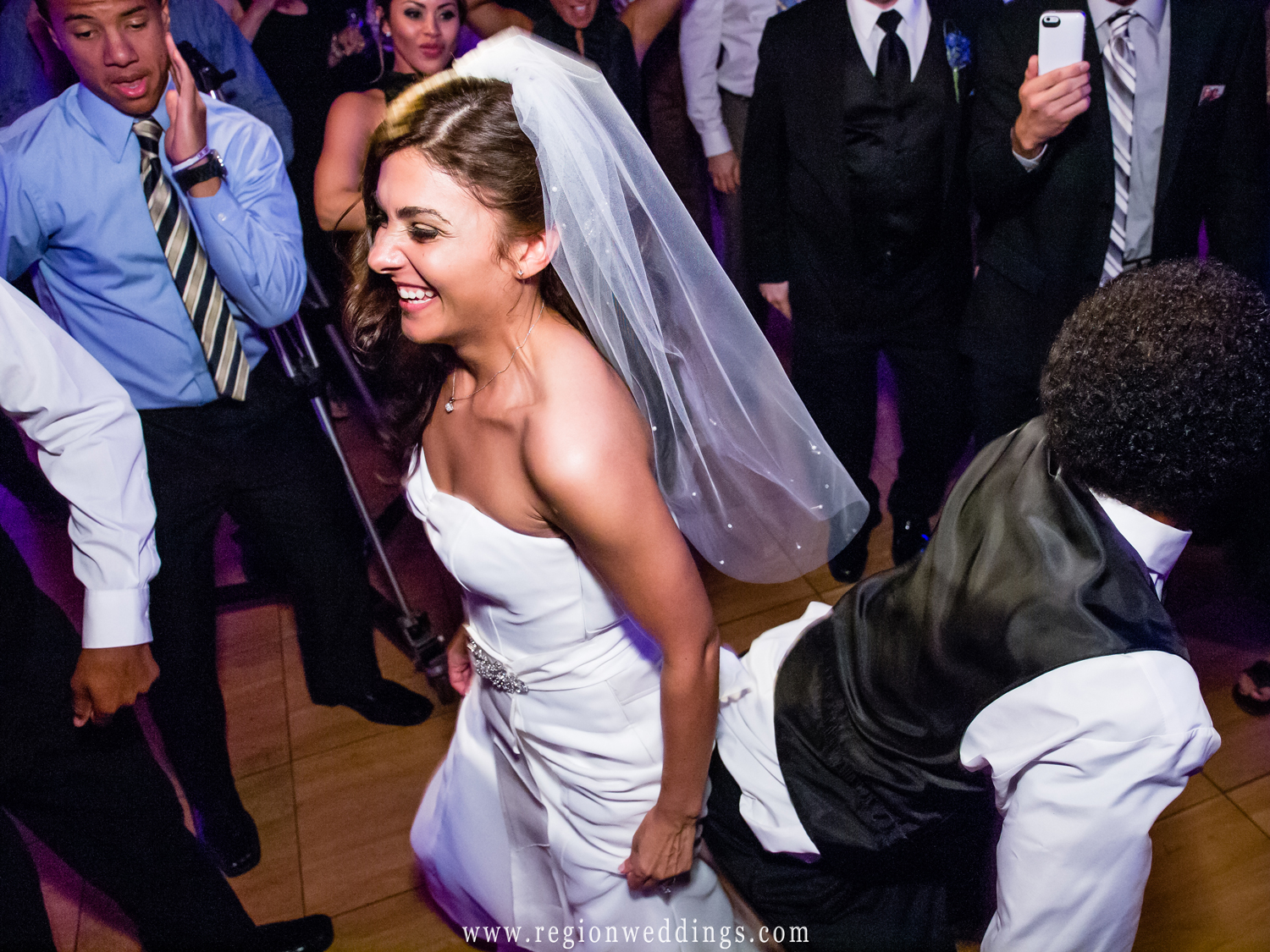 A bride shakes her booty as guests party at her wedding reception.