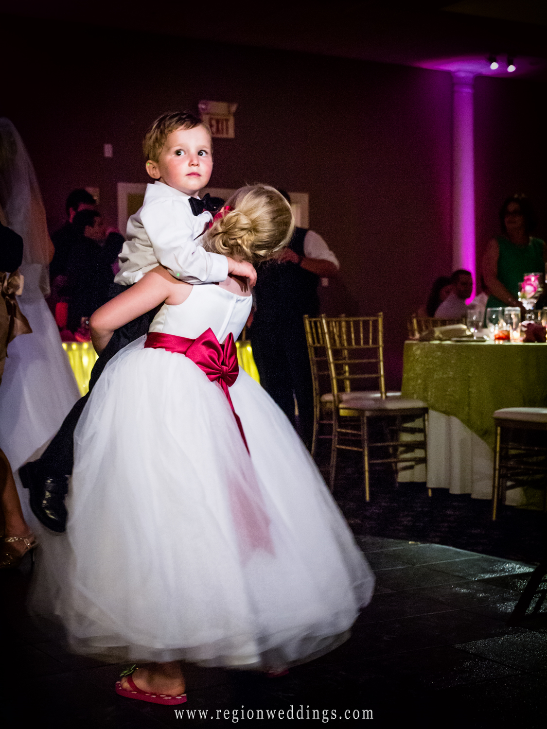 The ring bearer and flower girl have fun while dancing together.