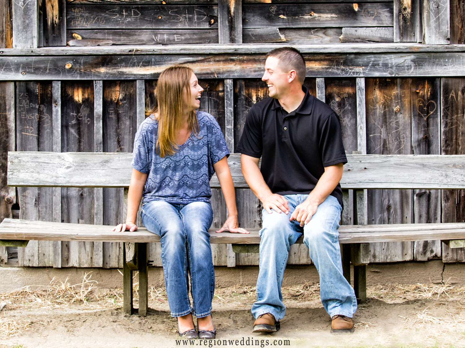 A candid engagement photo on the bench in front of the Sugar Shack in Deep River Park.