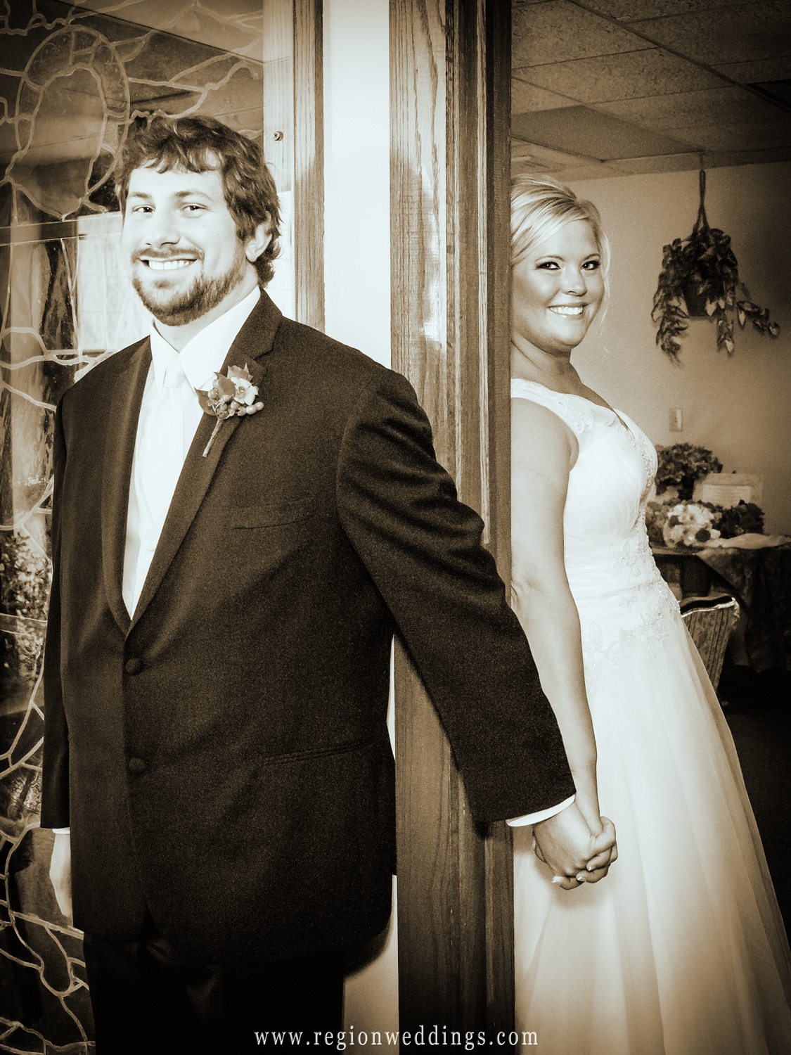 The bride and groom hold hands on each side of a door for their peek-a-boo almost first look wedding photo.