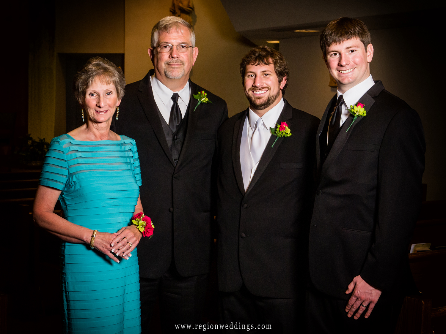 The groom poses for family wedding photos with his parents and brother.