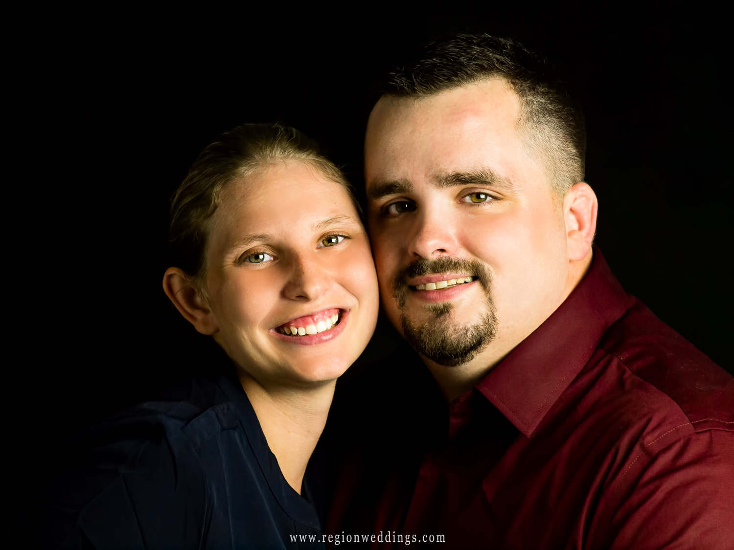 A cute couple poses for an engagement photo in studio.