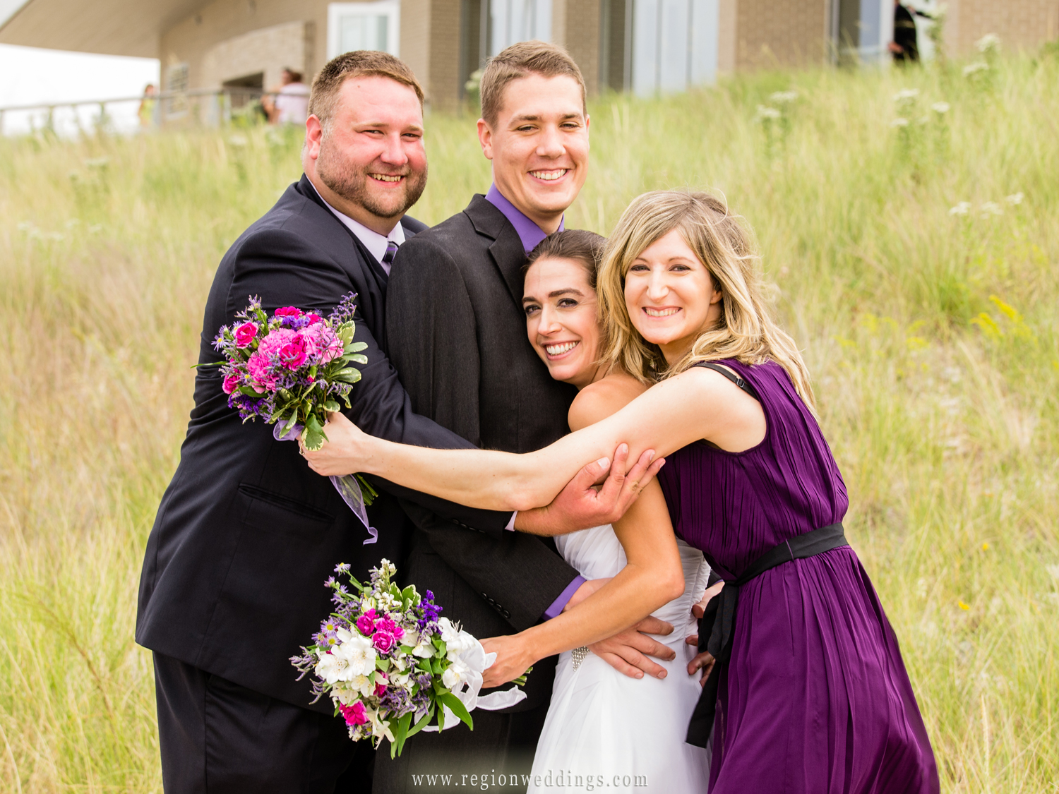 The best man and maid of honor engulf the bride and groom with a group hug on the beach of the Portage River Walk.