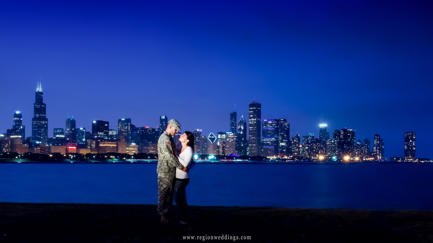 A soldier and his fiancé embrace in front of the Chicago Skyline at night for their engagement photo.